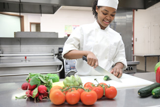 Culinary student cutting fruits and vegetables