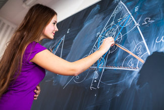 Female student solving math problem on blackboard